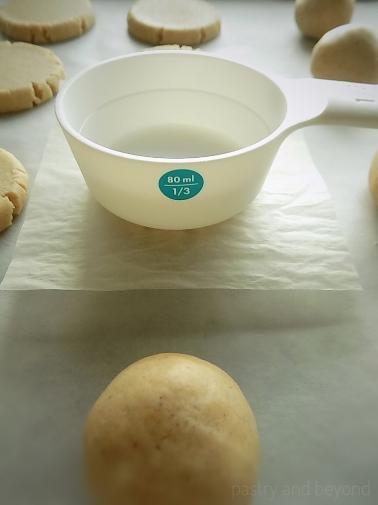 Flattening the cookie dough balls with a measuring cup.
