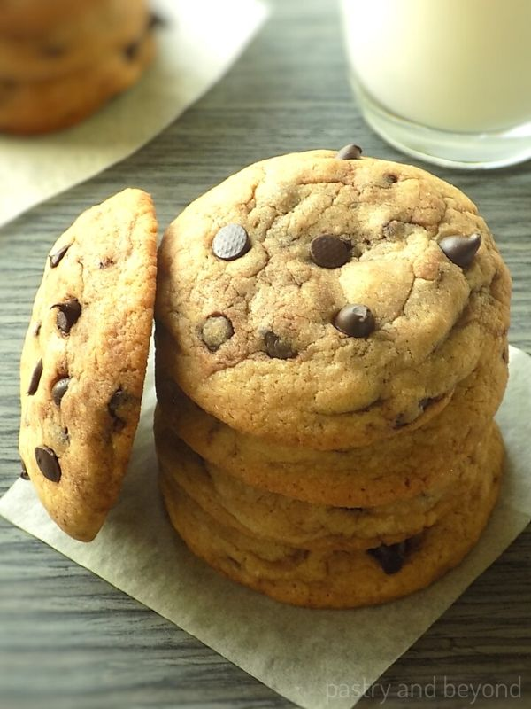 Stacked soft chocolate chip cookies on a parchment paper that is on a gray wooden surface with a cup of milk.
