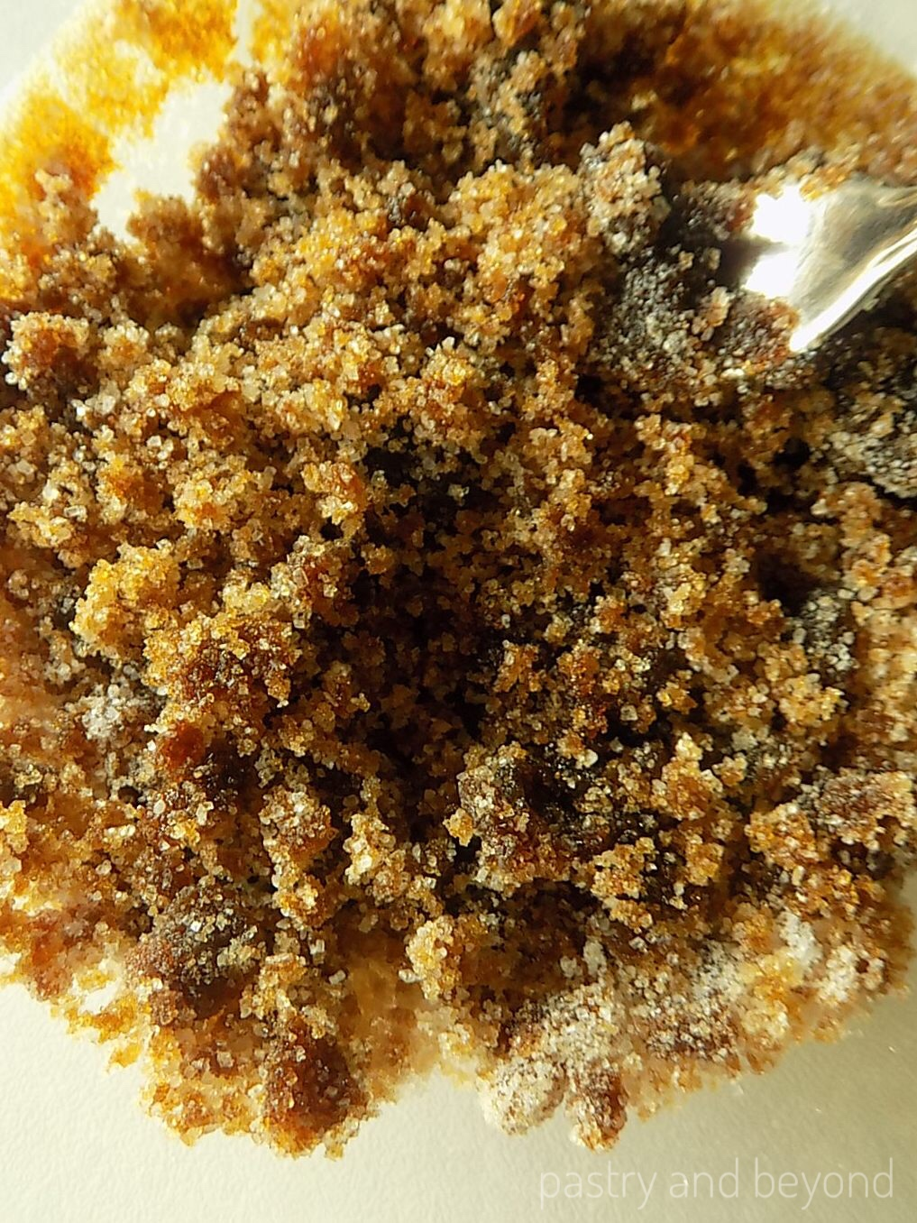 Steps of making homemade brown sugar: Mixing sugar and molasses with a fork.
