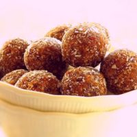 Almond date balls in a white bowl.