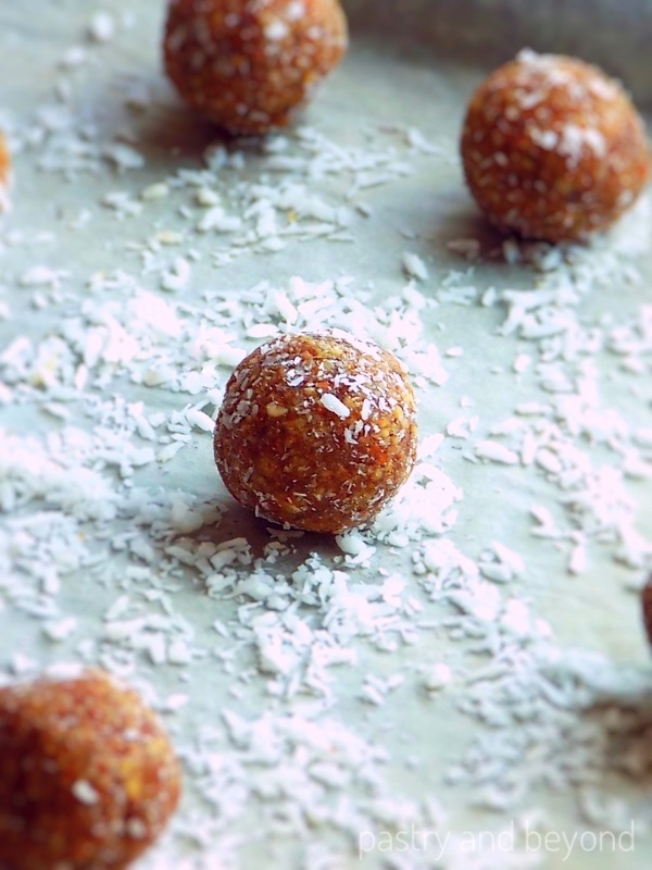 Almond energy balls on a shredded coconut covered surface.
