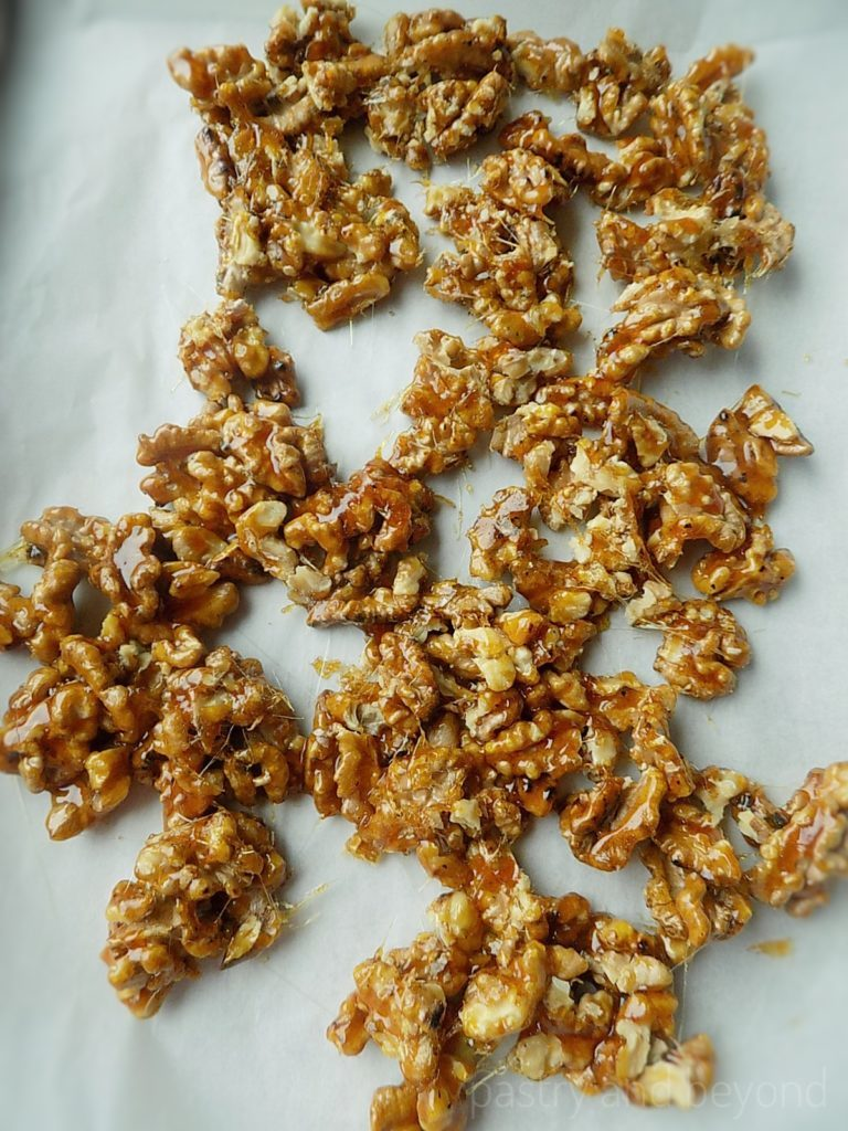 Caramelized walnuts on a parchment paper.