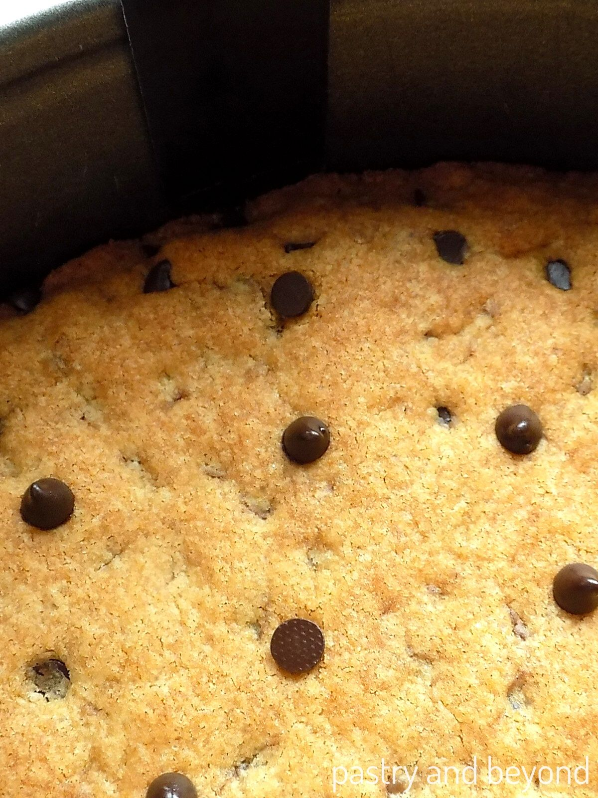 Loosening the cookie cake from the pan with a thin, small spatula.