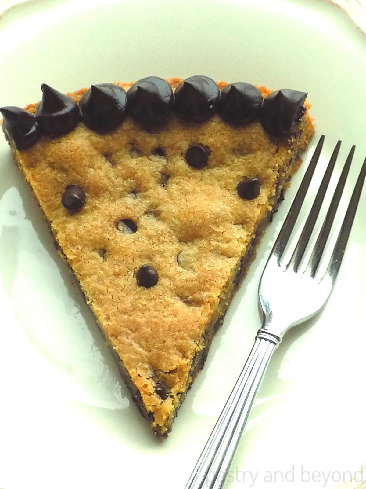 Chocolate chip cookie cake on a plate with a fork.