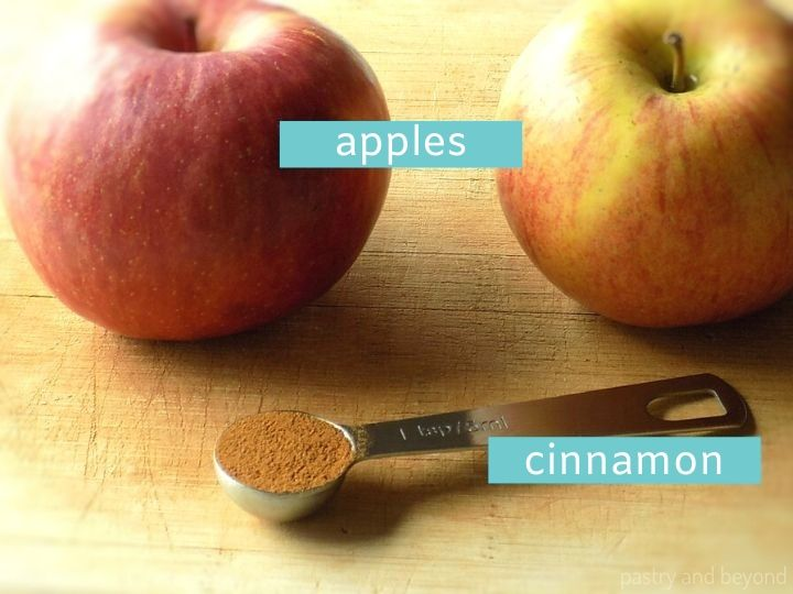 Two Gala apples and ground cinnamon in a teaspoon on a wooden surface with text overlay.