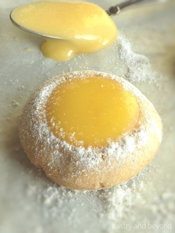 Thumbprint cookie with lemon curd and lemon curd on a spoon in the background.