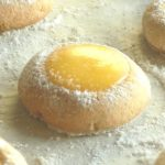 Lemon curd thumbprint cookies with powdered sugar on the edges.