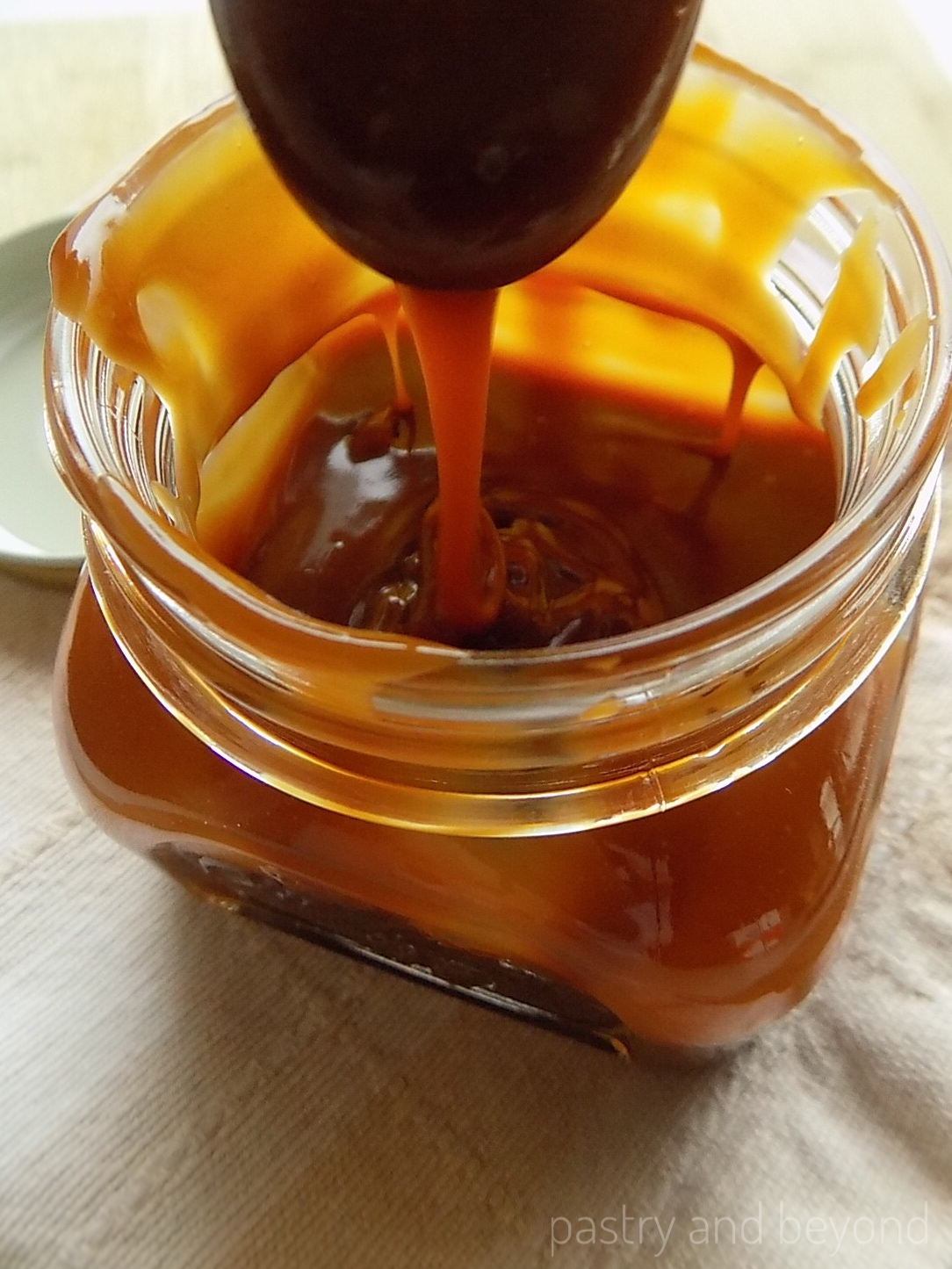 Homemade Caramel Sauce dripping from a spoon.