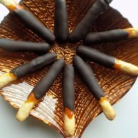 Caramel and chocolate sticks on a brown plate.