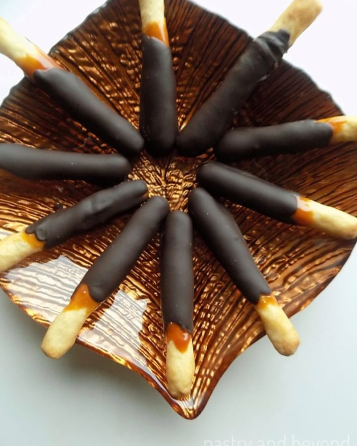 Caramel and chocolate cookie sticks on a brown glass plate.