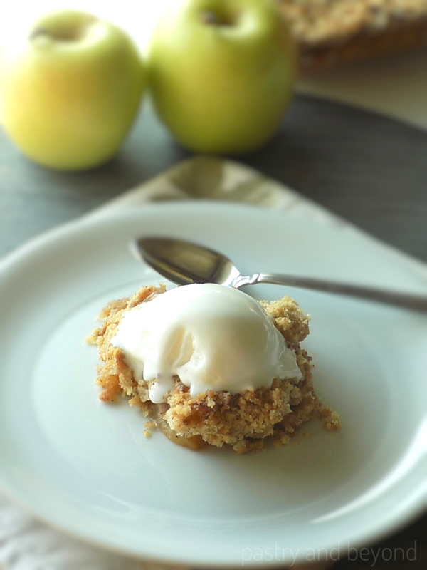 Apple crumble topped with ice cream on a plate and golden apples are in the background.