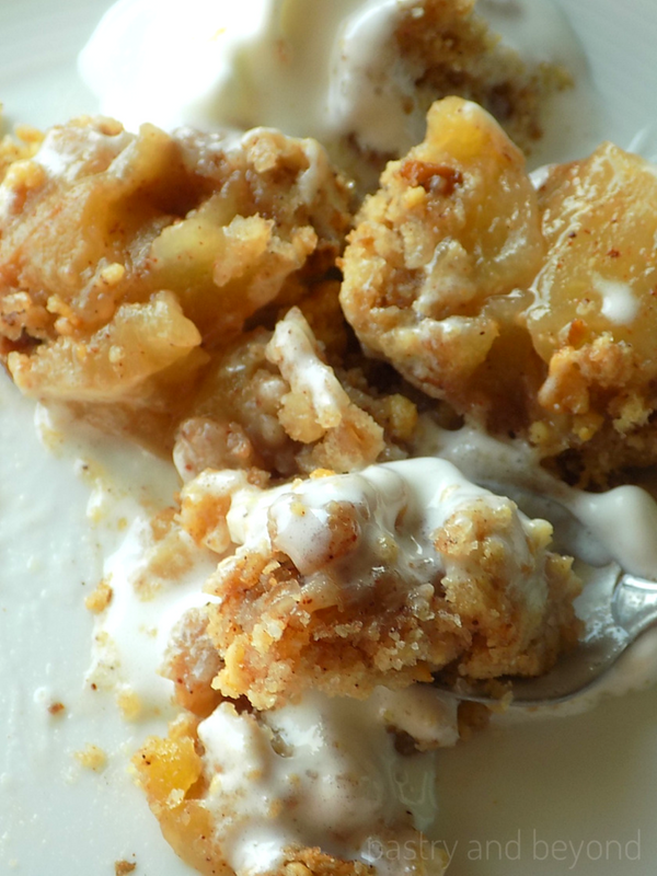 Spooned apple crumble with ice cream.