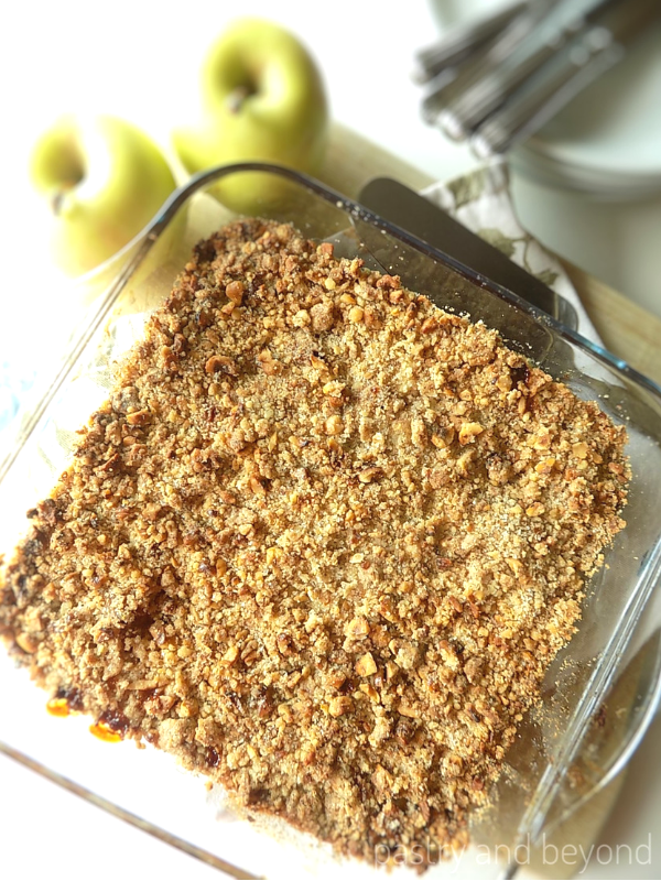 Overhead view of apple crumble on a baking dish with apples, plates, forks in the background.