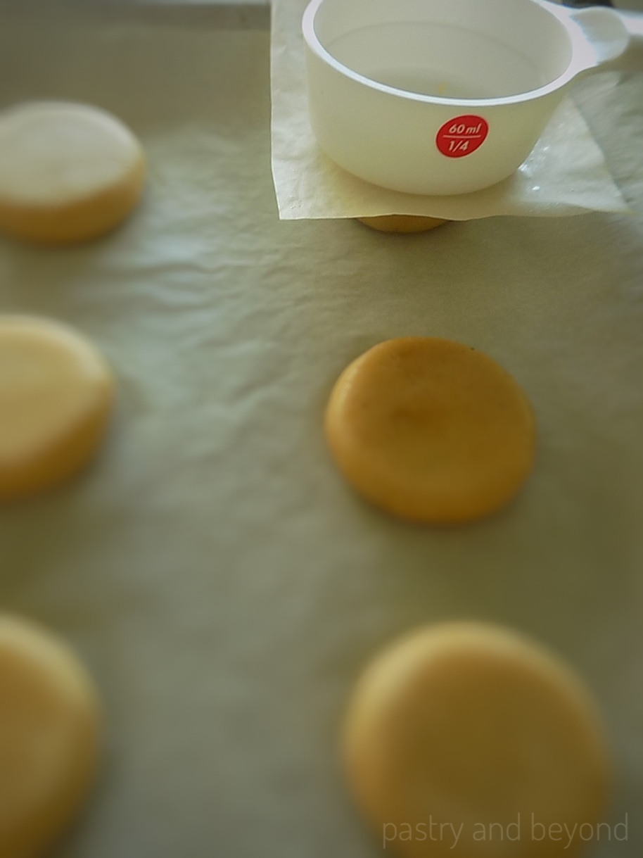 Steps of Making Ginger Thumbprint Cookies: Flattening the balls with a back of measuring cup