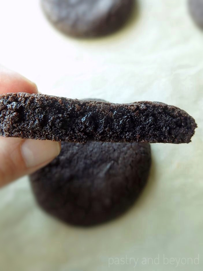 Holding half of a chocolate cookie.