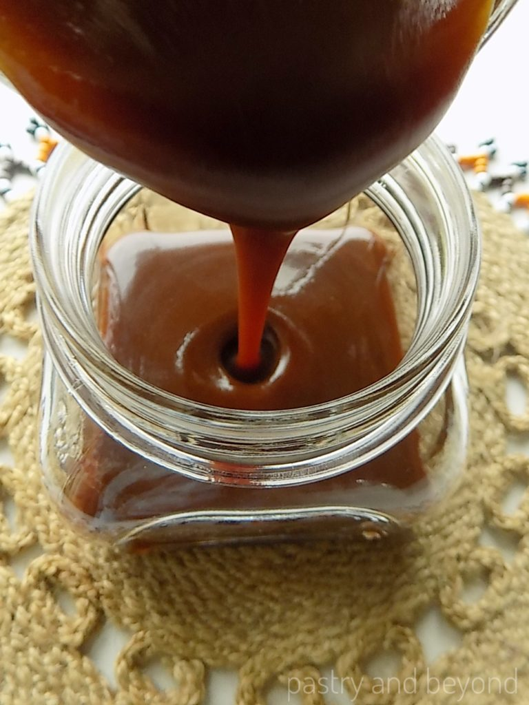 Pouring homemade caramel sauce from a pan into a jar.