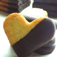 Heart shaped coconut cookies that are dipped into melted semisweet chocolate.