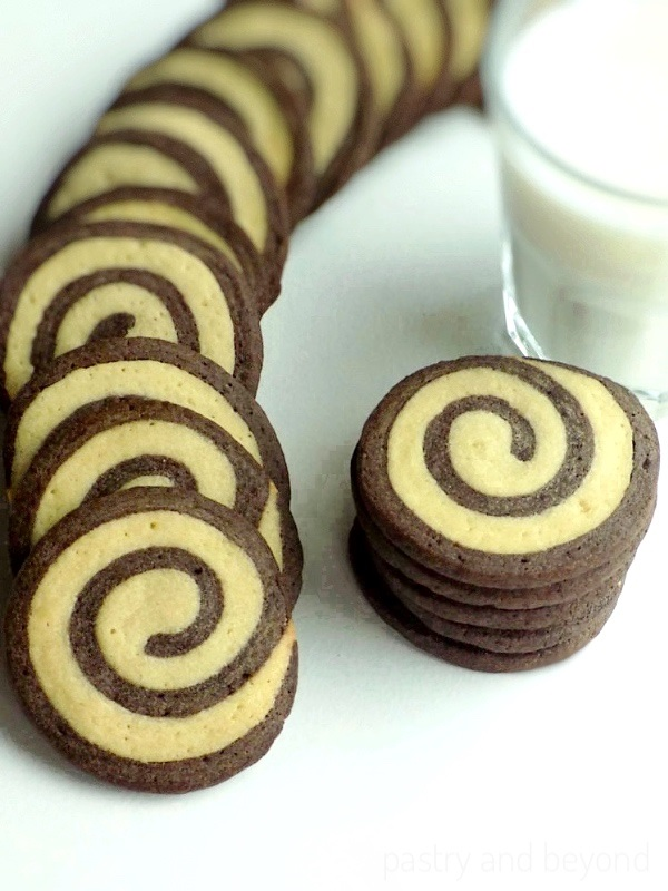 Vanilla and chocolate swirl cookies with a glass of milk.