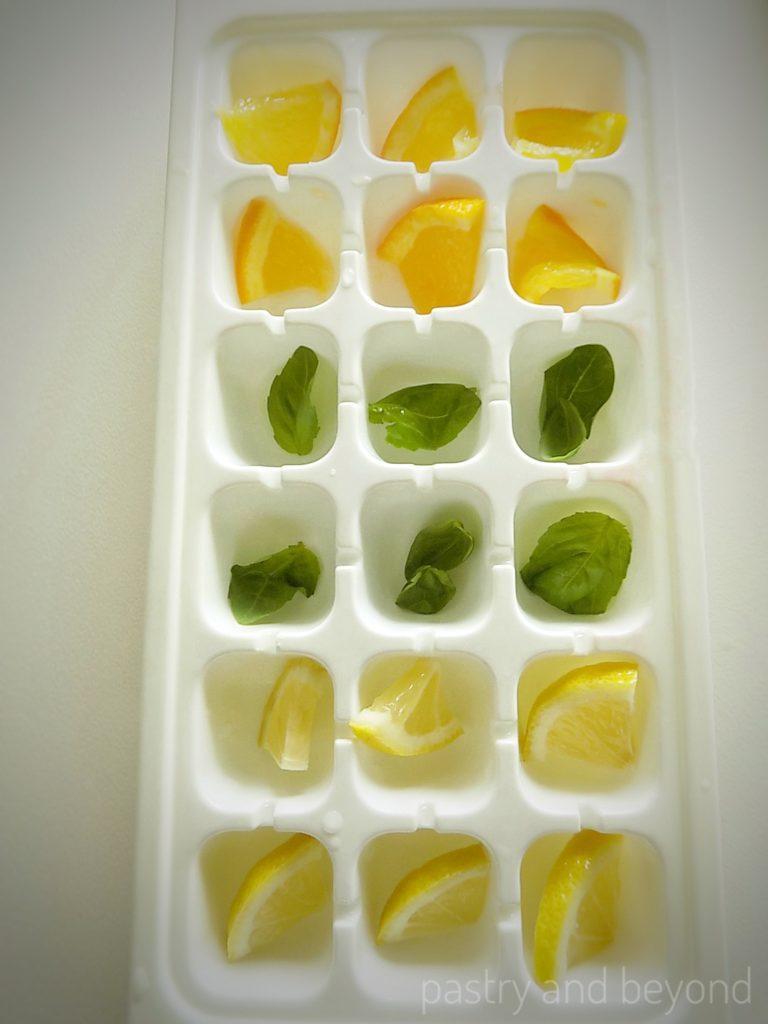 Placing lemon, orange , basil leaves into the ice tray.