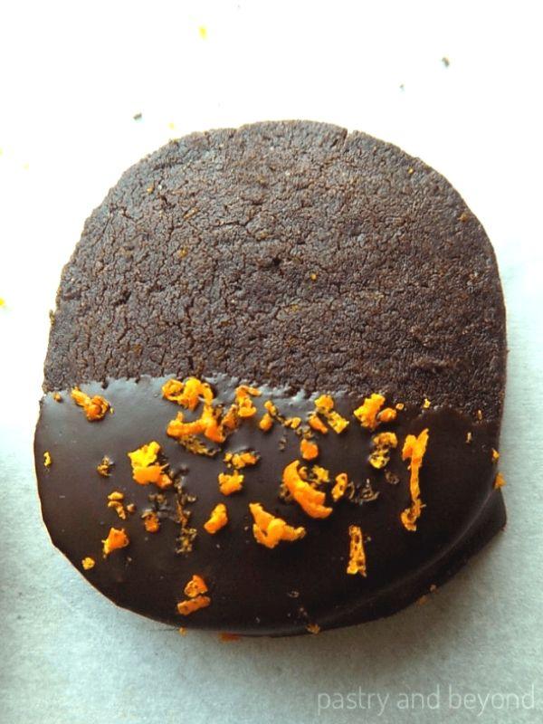 Chocolate orange shortbread cookie dipped in melted semi sweet chocolate, orange zest sprinkled on top.