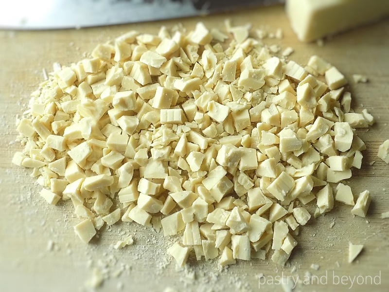 Roughly chopped white chocolate on a chopping board.