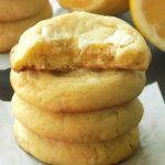 Stacked lemon white chocolate cookies, half of the cookie on top, lemons in the background.