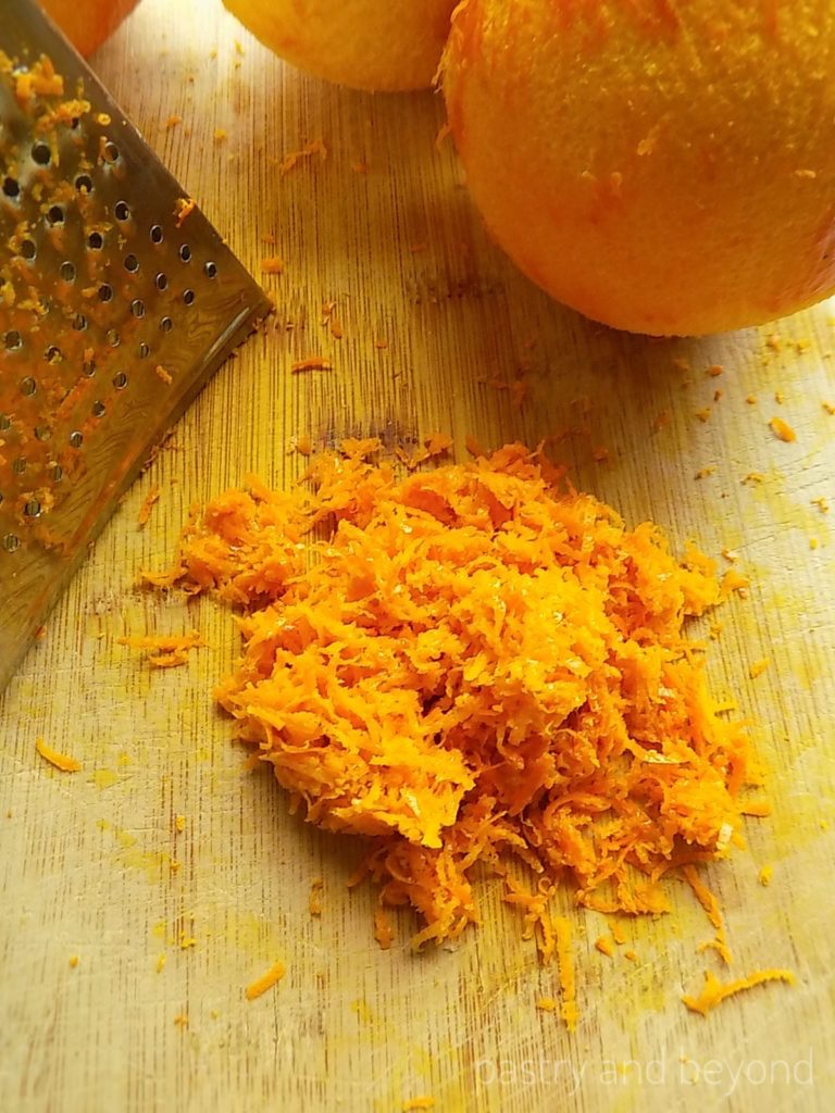 Orange zest, grater and oranges on a wooden board.