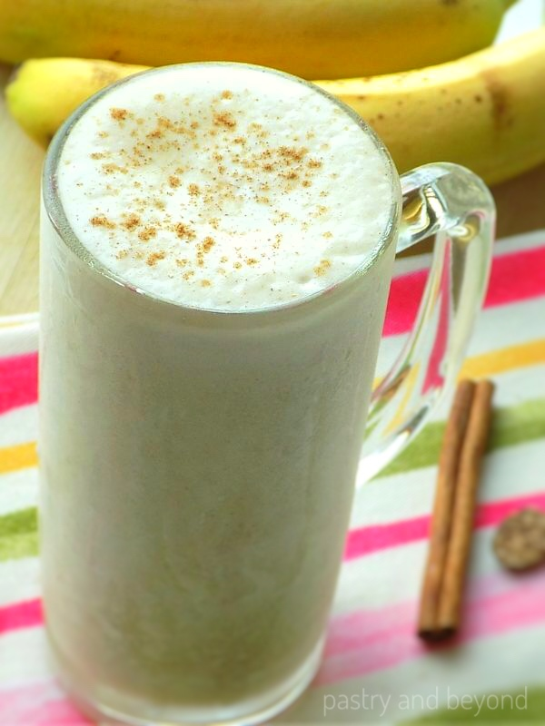 Banana smoothie with ground cinnamon on top and bananas in the background.