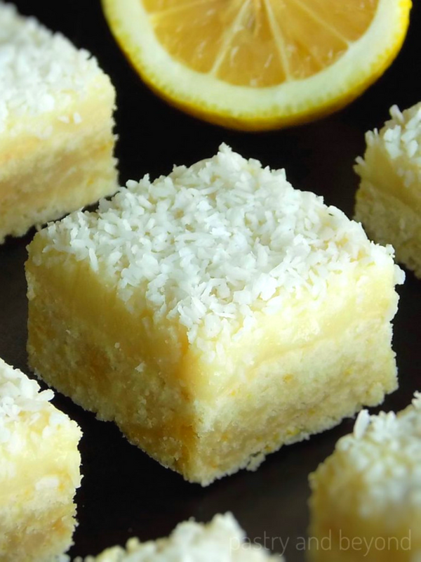 Lemon coconut bars and a half lemon on a black surface.