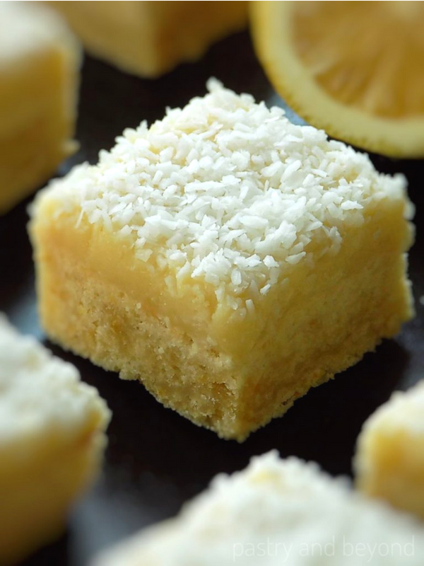 Lemon coconut squares on a black surface.