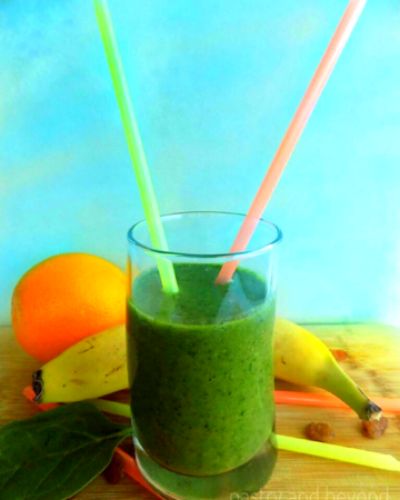 Green iron rich smoothie in a glass with straws, banana and orange in the background.
