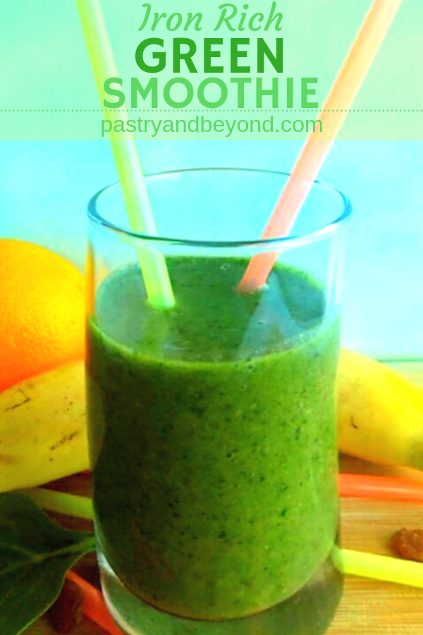 Green smoothie in a glass with straws.