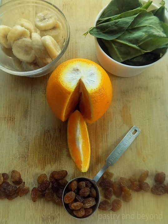 Orange, raisins, banana slices, spinach
