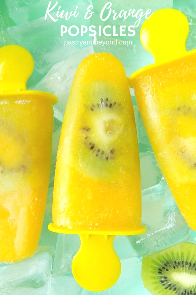 Orange popsicles with kiwi slices in a bowl that is full of ice cubes.