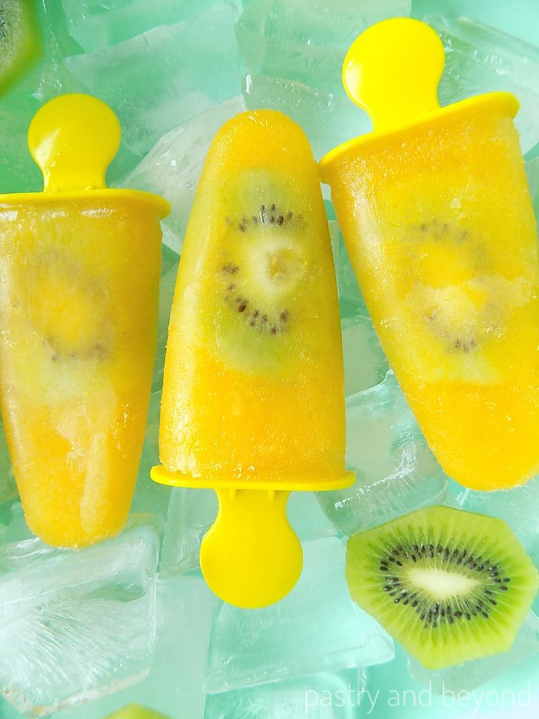Orange and kiwi popsicles on ice cubes.