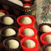 Peppermint chocolate truffles in mini cupcake liners and other truffles in a box in the background.