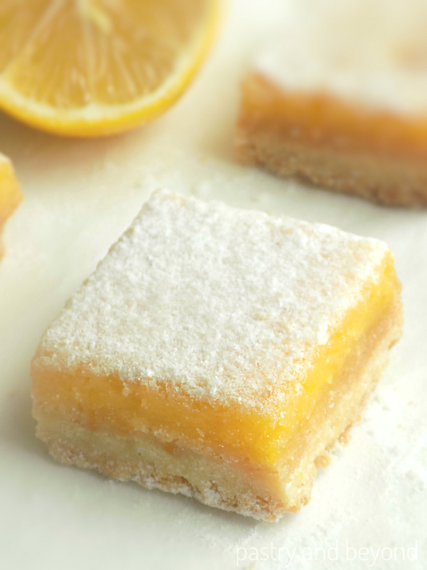 Lemon bars on a white surface with lemon in the background.