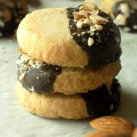 Stacked chocolate dipped almond shortbread cookies with crushed almonds on top on parchment paper.