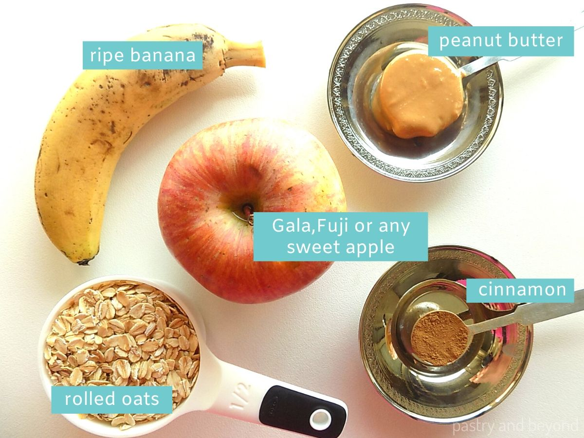 Ingredients for healthy apple oatmeal cookies on a white surface.
