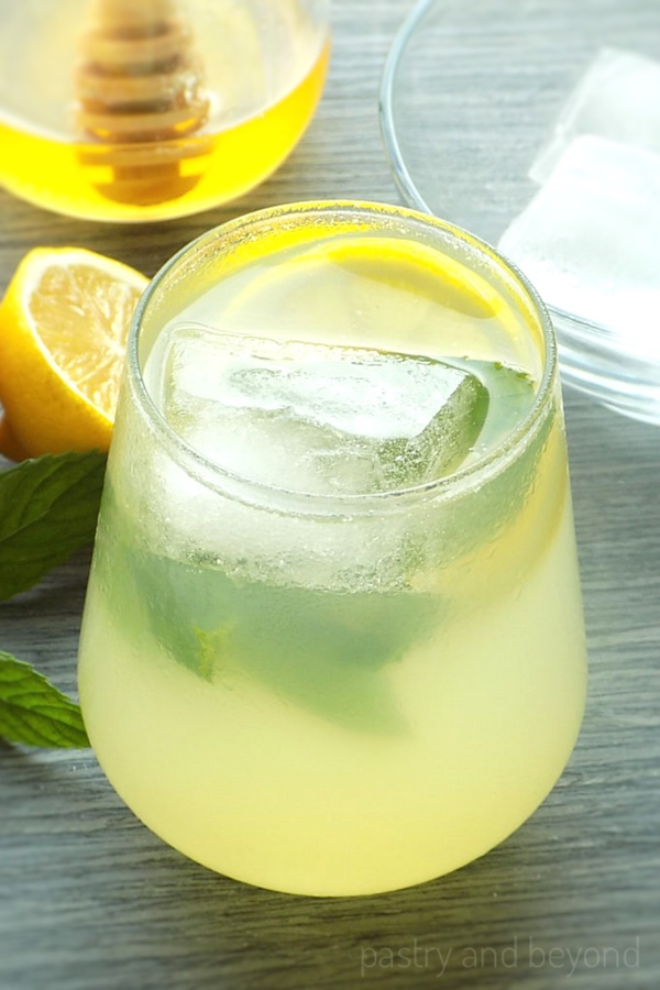 Lemonade with honey and mint on a blue-gray surface.