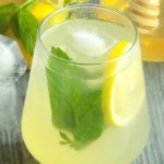 Honey lemonade in a glass with lemon slice and mint leaves.