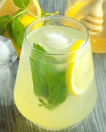 Honey lemonade in a glass with lemon slice and mint leaves.