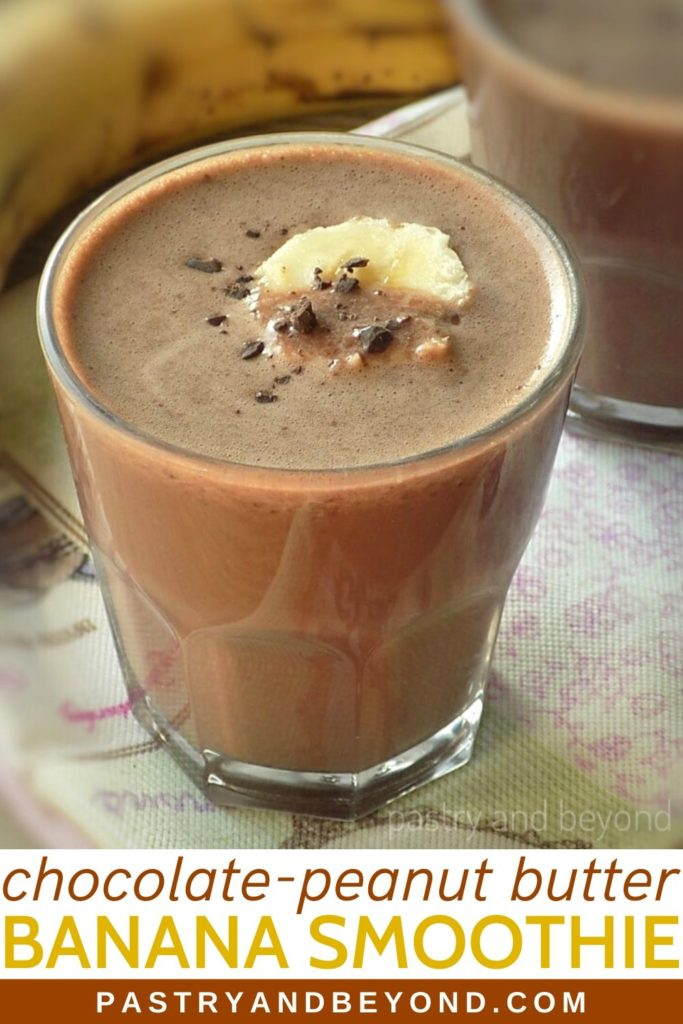 Chocolate Peanut Butter Banana Smoothie in a glass with shredded chocolate and slice of banana on top.