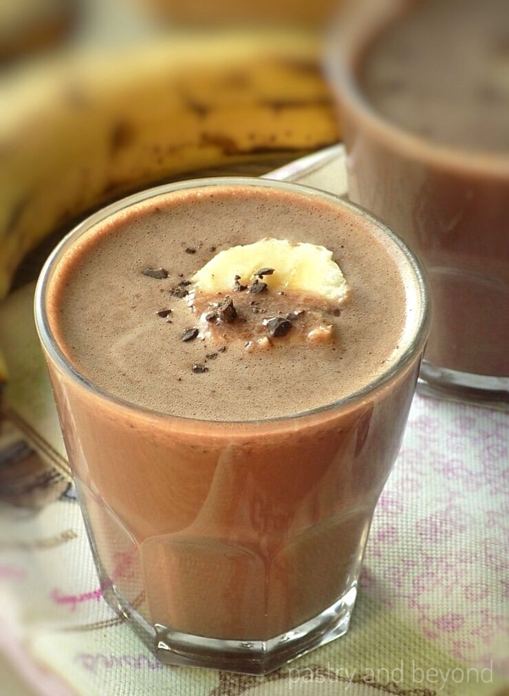 Chocolate peanut butter smoothie in two glasses with a banana in the background.