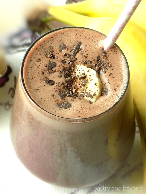 Chocolate peanut butter banana smoothie with shredded chocolate and banana slice on top.