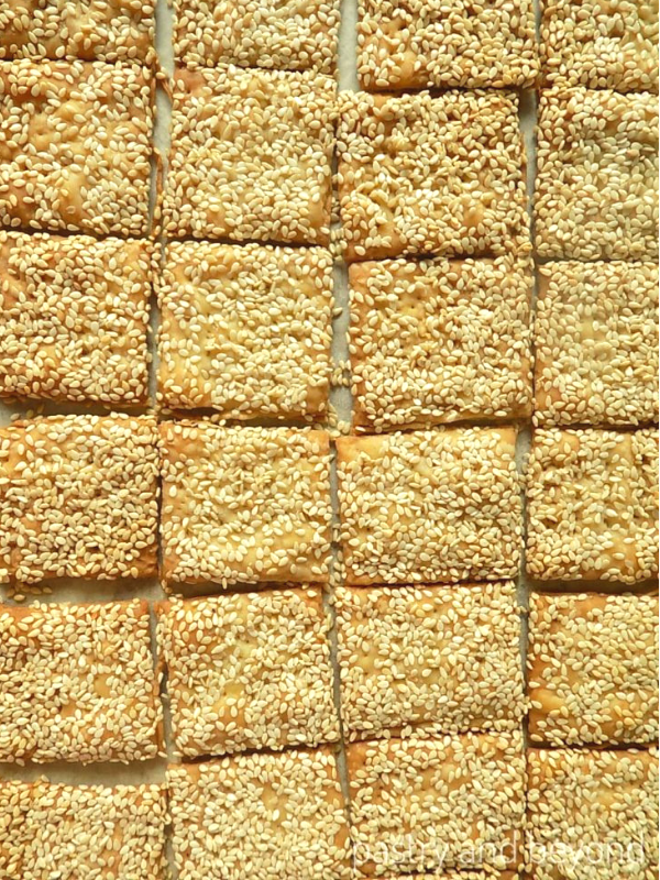 Small square sesame crackers on a parchment paper.
