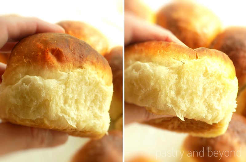 A hand is holding and squeezing the soft dinner roll to show is fluffiness.