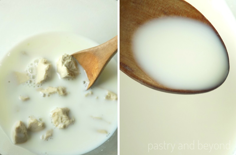 Fresh yeast is dissolved with milk using a wooden spoon in a small glass bowl.