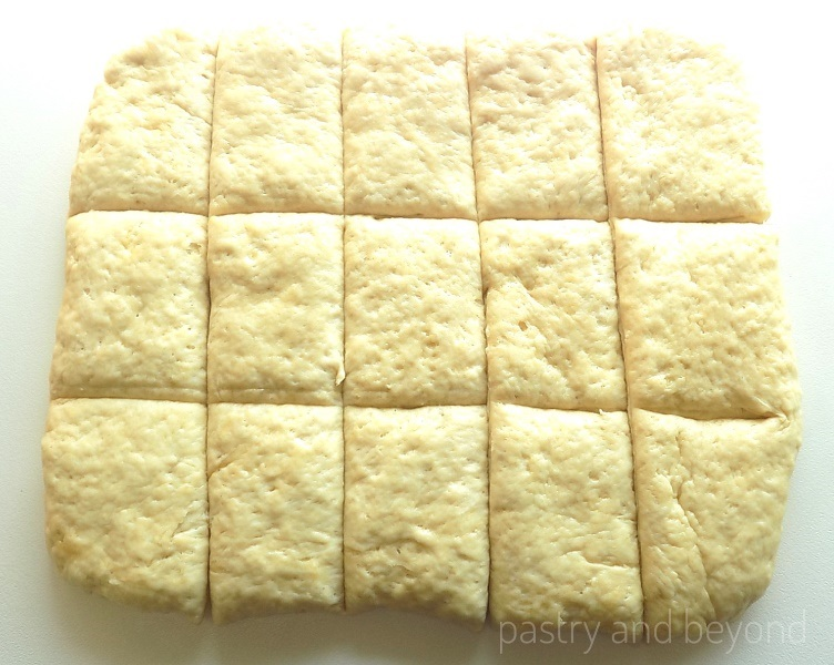 Making a rectangle out of the dough and cut into fifteen pieces on a work surface.