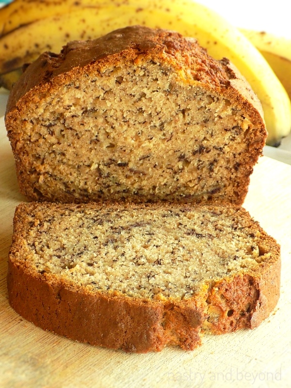 Banana bread on a wooden board with bananas in the background.